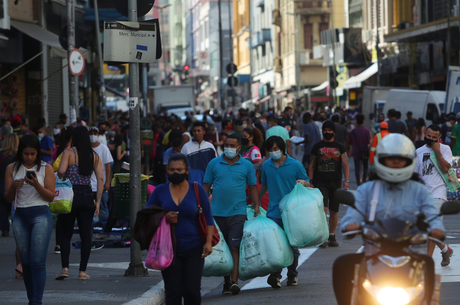 People walk with bags at a popular shopping street, Sao Paulo, Brazil, June 19, 2020. (REUTERS Photo)
