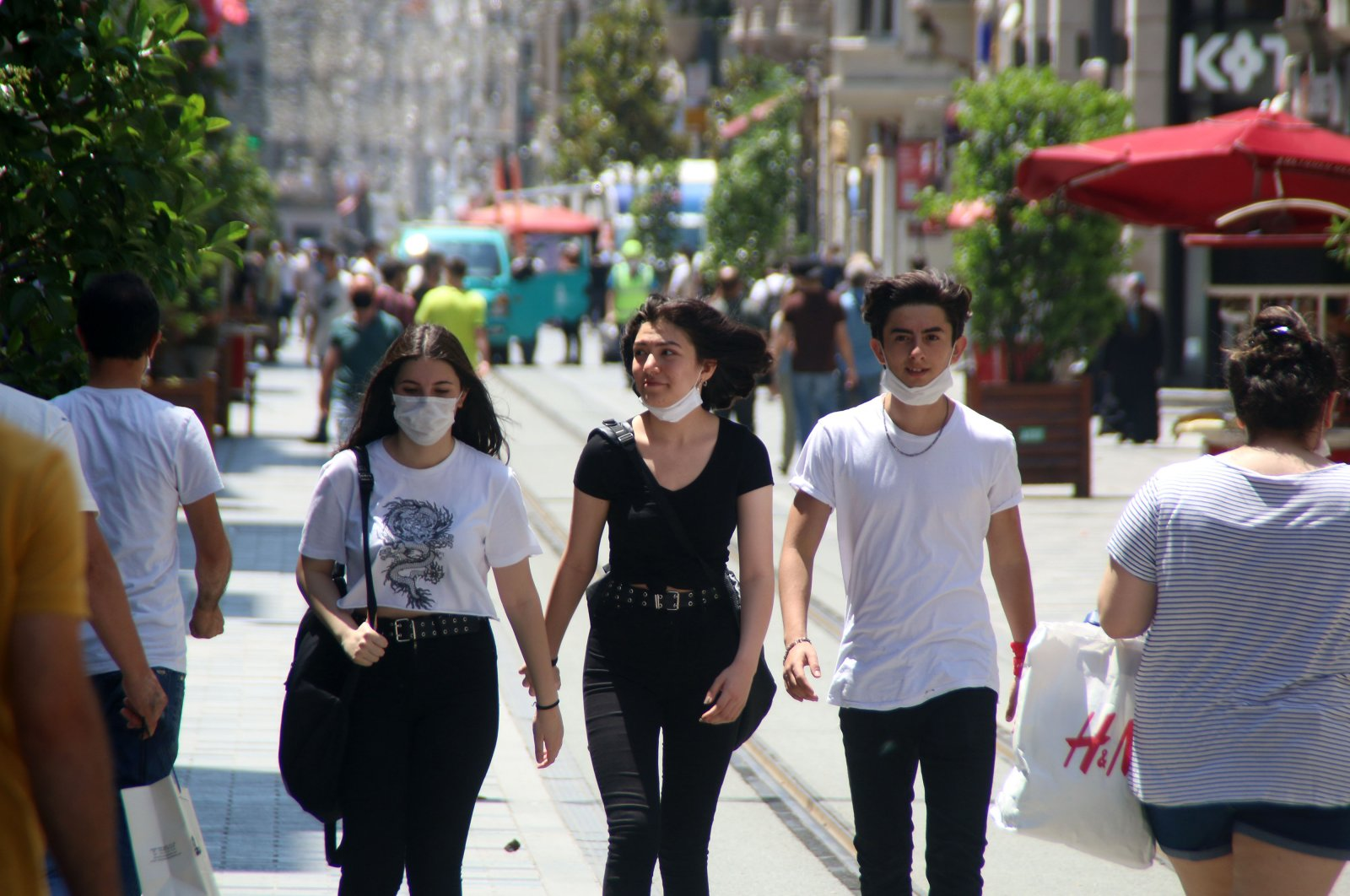 One person properly wears a mask, as two others keep theirs open on İstiklal Avenue, in Istanbul, Turkey, June 21, 2020. (DHA Photo)