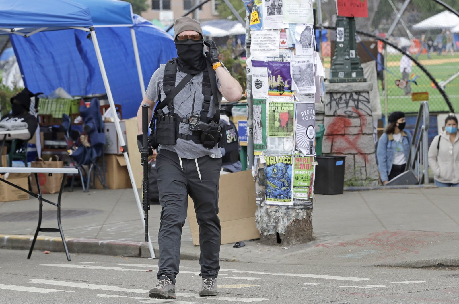 A person carries a rifle as he walks near what has been named the Capitol Hill Occupied Protest (CHOP) zone, Seattle, June 20, 2020