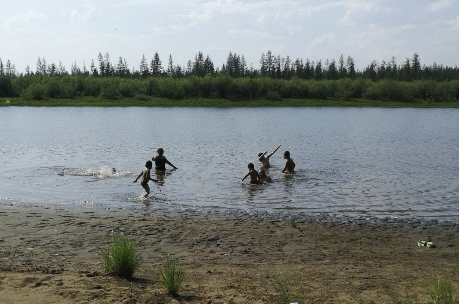 In this handout photo provided by Olga Burtseva, children play in the Krugloe Lake outside Verkhoyansk, the Sakha Republic, Russia, June 21, 2020. (AP Photo)
