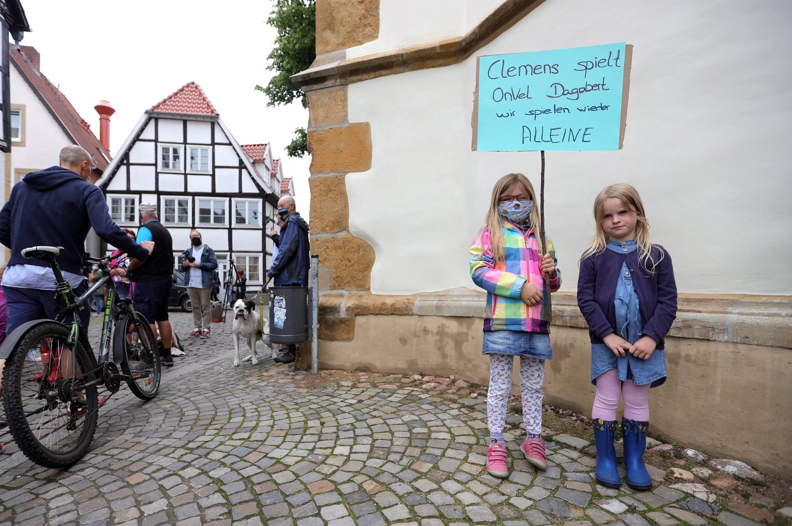 Two children pose with a sign reading 'Clemens plays Uncle Scrooge, we play alone again' as they protest against the closure of schools and kindergartens in Rheda-Wiedenbrueck, western Germany, 18 June 2020. (EPA Photo)
