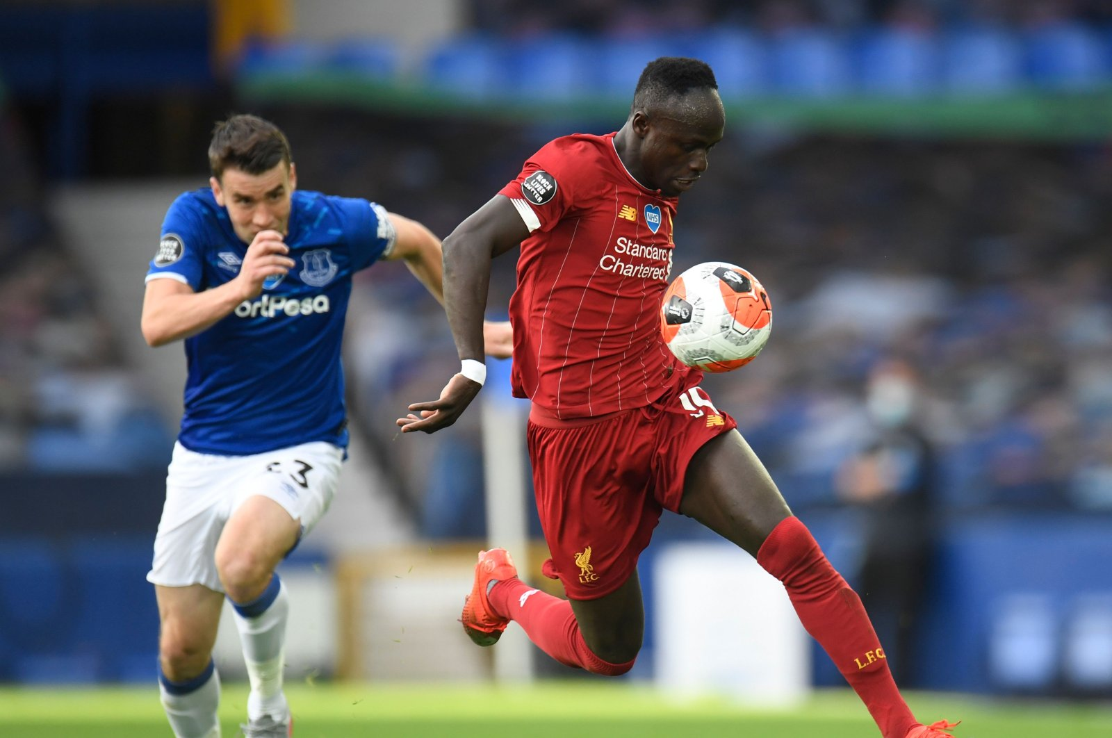 Liverpool's Sadio Mane (R) controls the ball during a match against Everton, in Liverpool, England, June 21, 2020. (AFP Photo)