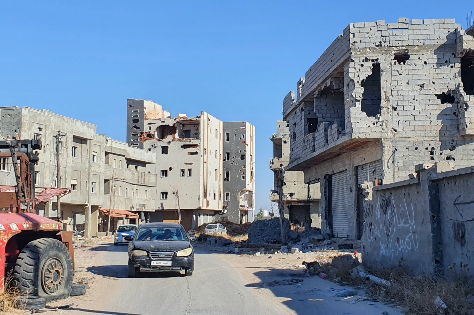 Cars advance on an empty road lined with damaged buildings in the Salaheddin district south of the Libyan capital Tripoli, as some residents return to the area after it was demined, June 21, 2020. (AFP Photo)