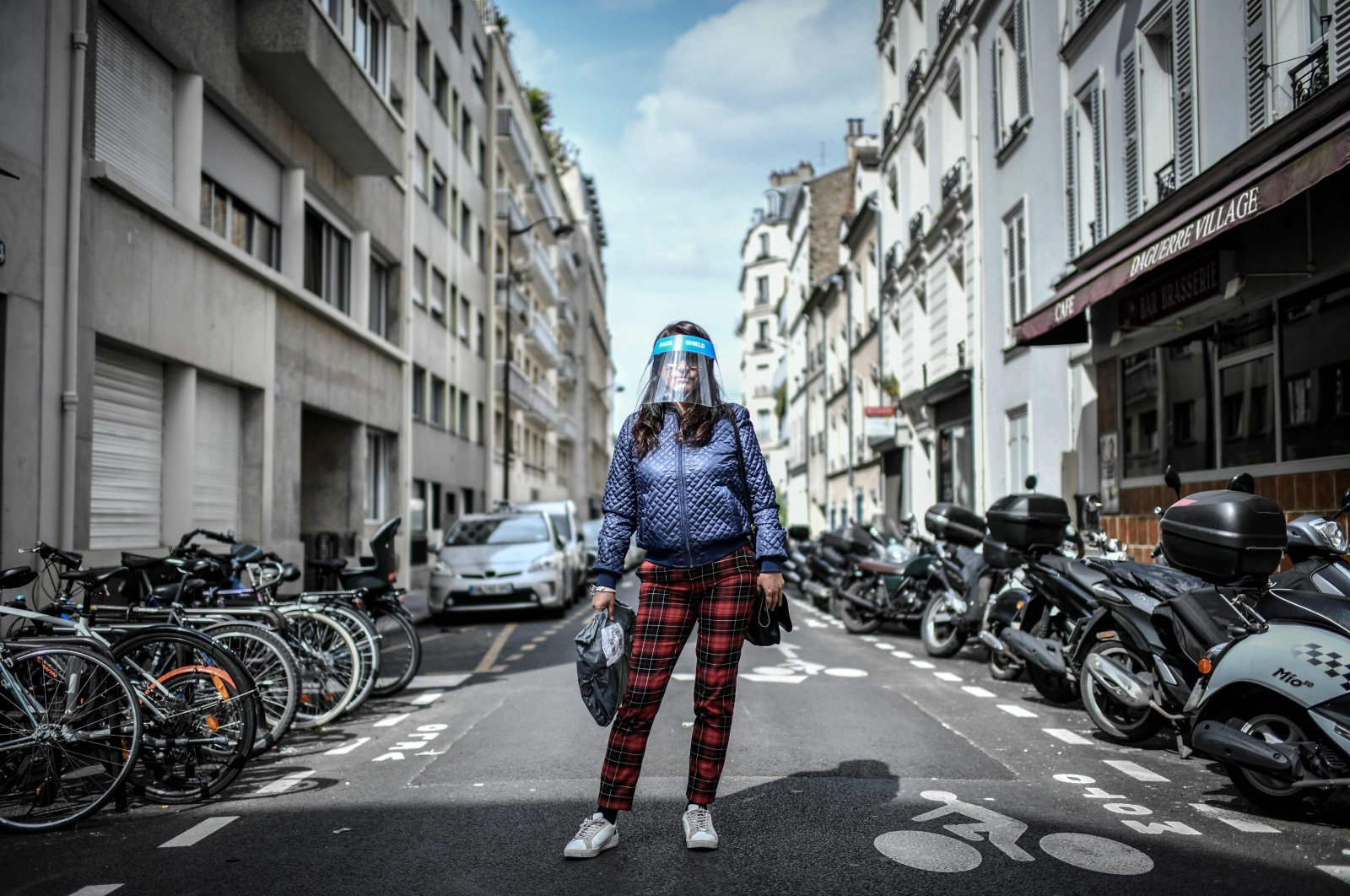 A woman, wearing a protective face shield, poses for a photograph in the streets of Paris, France, May 4, 2020. (AFP Photo)