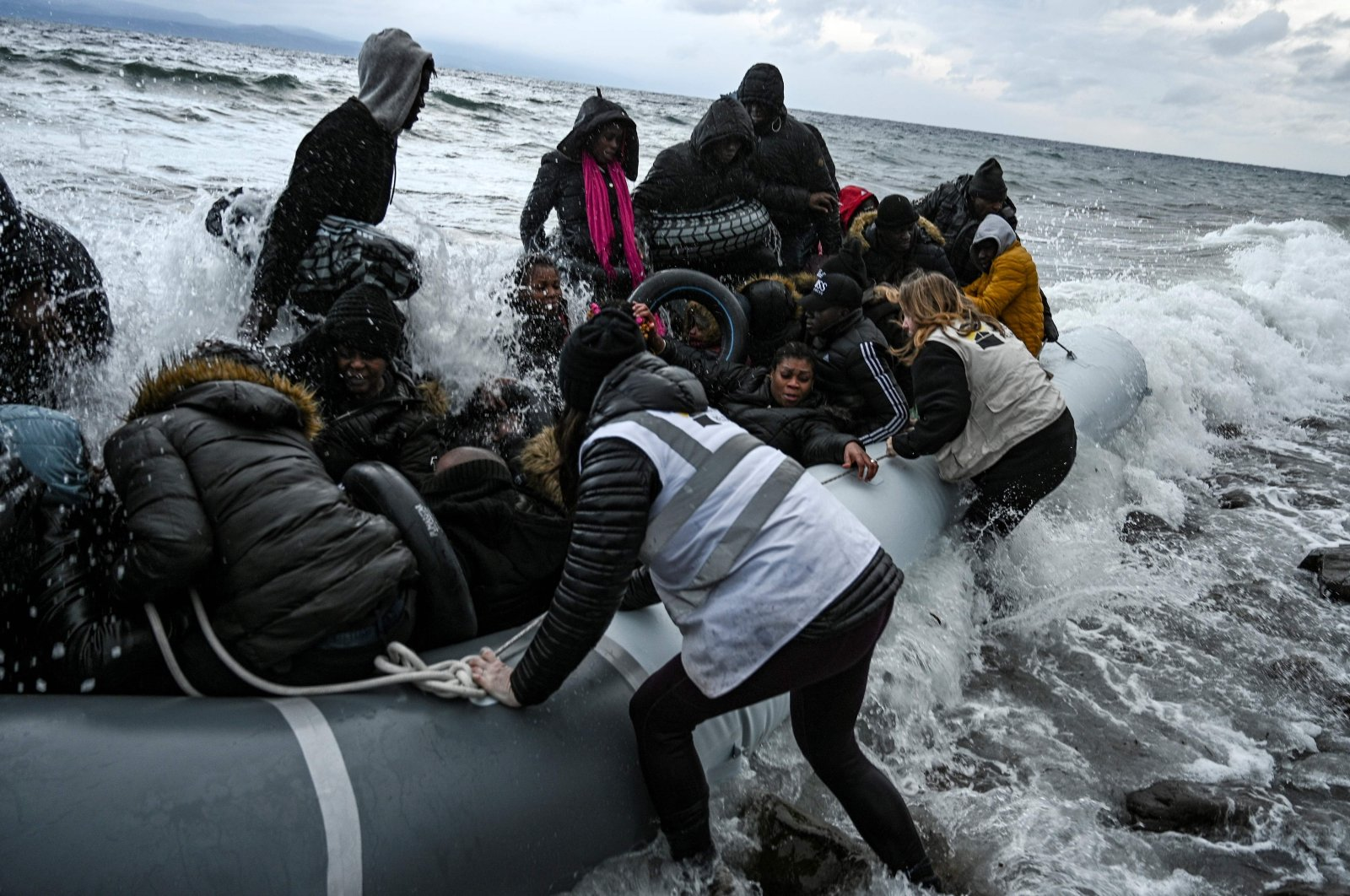 Volunteers help refugees and migrants from the Gambia and the Republic of Congo who were rescued near Lesbos island by a warship during their sea crossing between Turkey and Greece, Feb. 29, 2020. (AFP Photo)