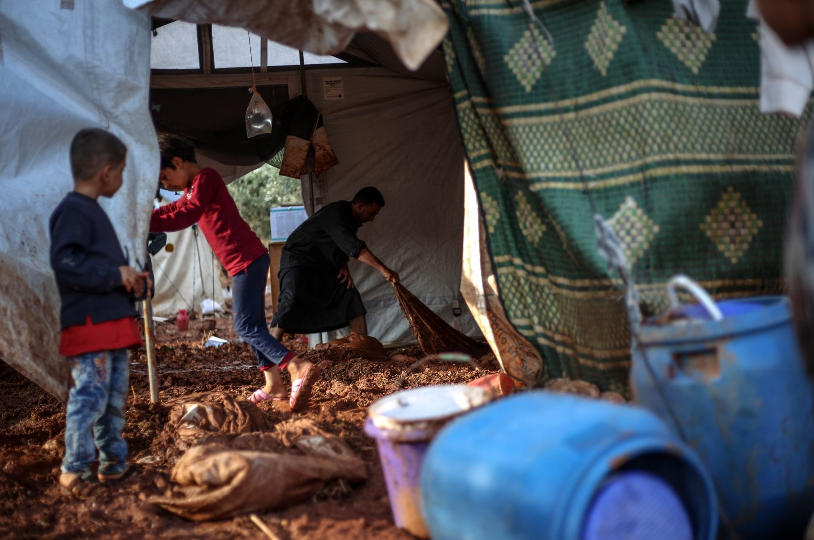A displaced Syrian family is seen clearing mud from their tent after heavy rains caused devastating damage in camps in northwestern Syria, June 19, 2020. (AA Photo)