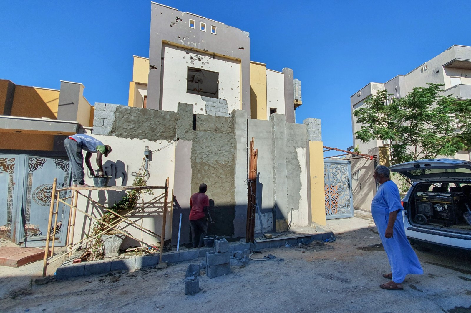 A Libyan man inspects workers renovating a damaged home in the Salaheddin district south of the capital Tripoli, June 21, 2020. (AFP Photo)