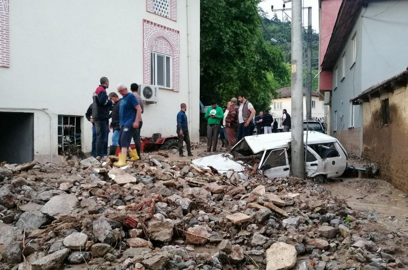 People look at debris left by floods in Dudaklı village, in Bursa, Turkey, June 22, 2020. (IHA Photo)