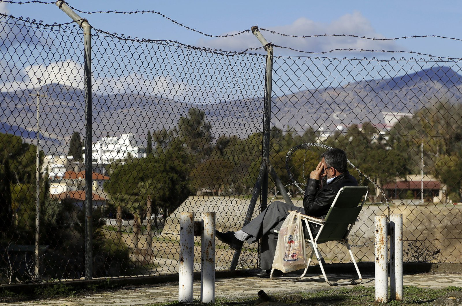 A man sits in front of the fence that divides the Greek and Turkish Cypriot areas on the Eastern Mediterranean island of Cyprus, Jan. 11, 2017. (AP Photo)