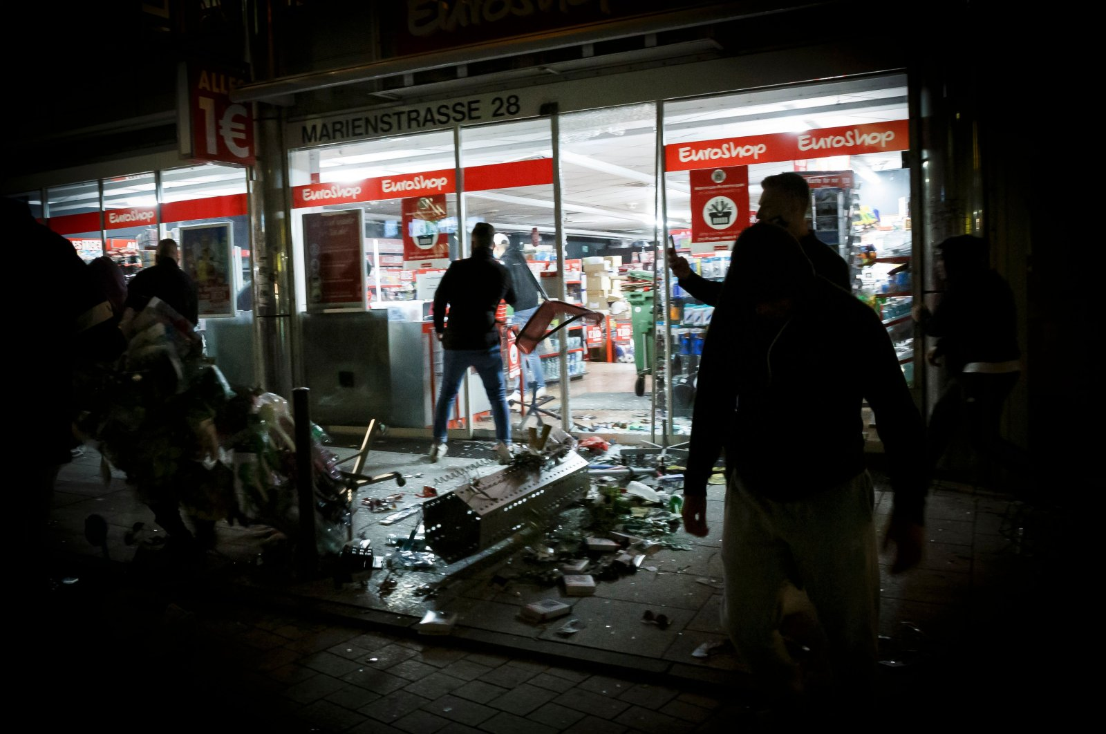 People stand in front of a shop that was plundered during riots in Stuttgart, southern Germany, June 21, 2020. (AFP Photo)