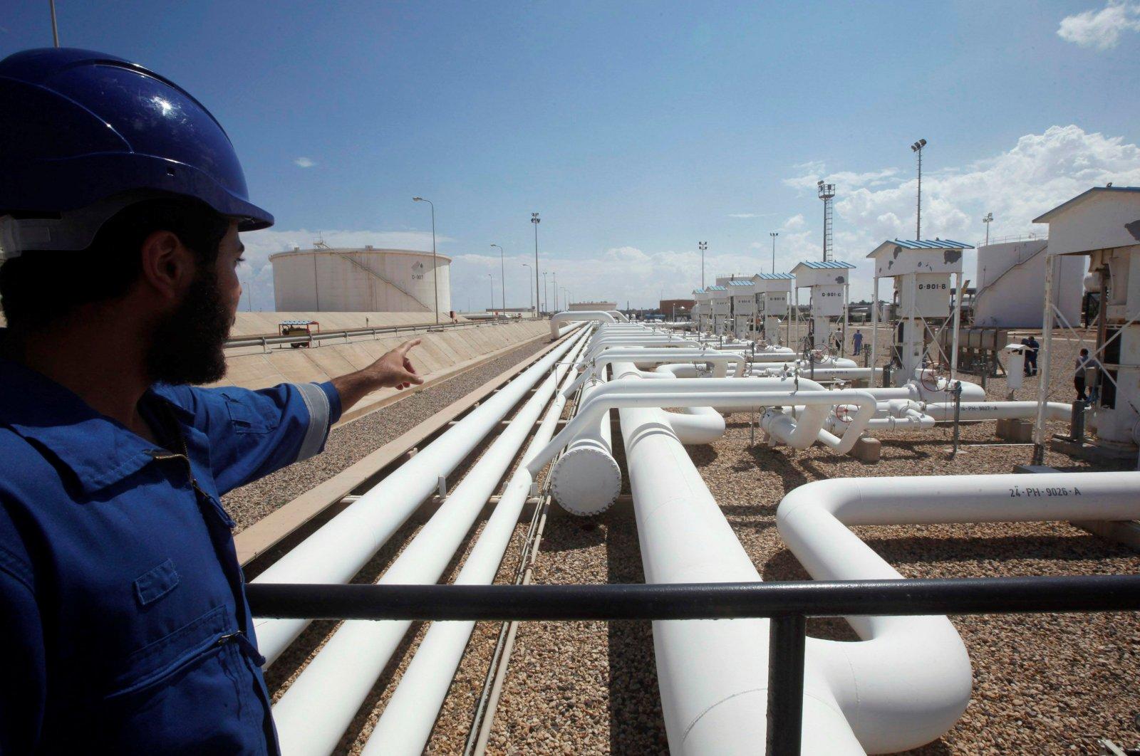 A worker gestures toward pipelines at the Zawiya Oil Refinery, Zawiya, Libya, Aug. 22, 2013. (Reuters Photo)
