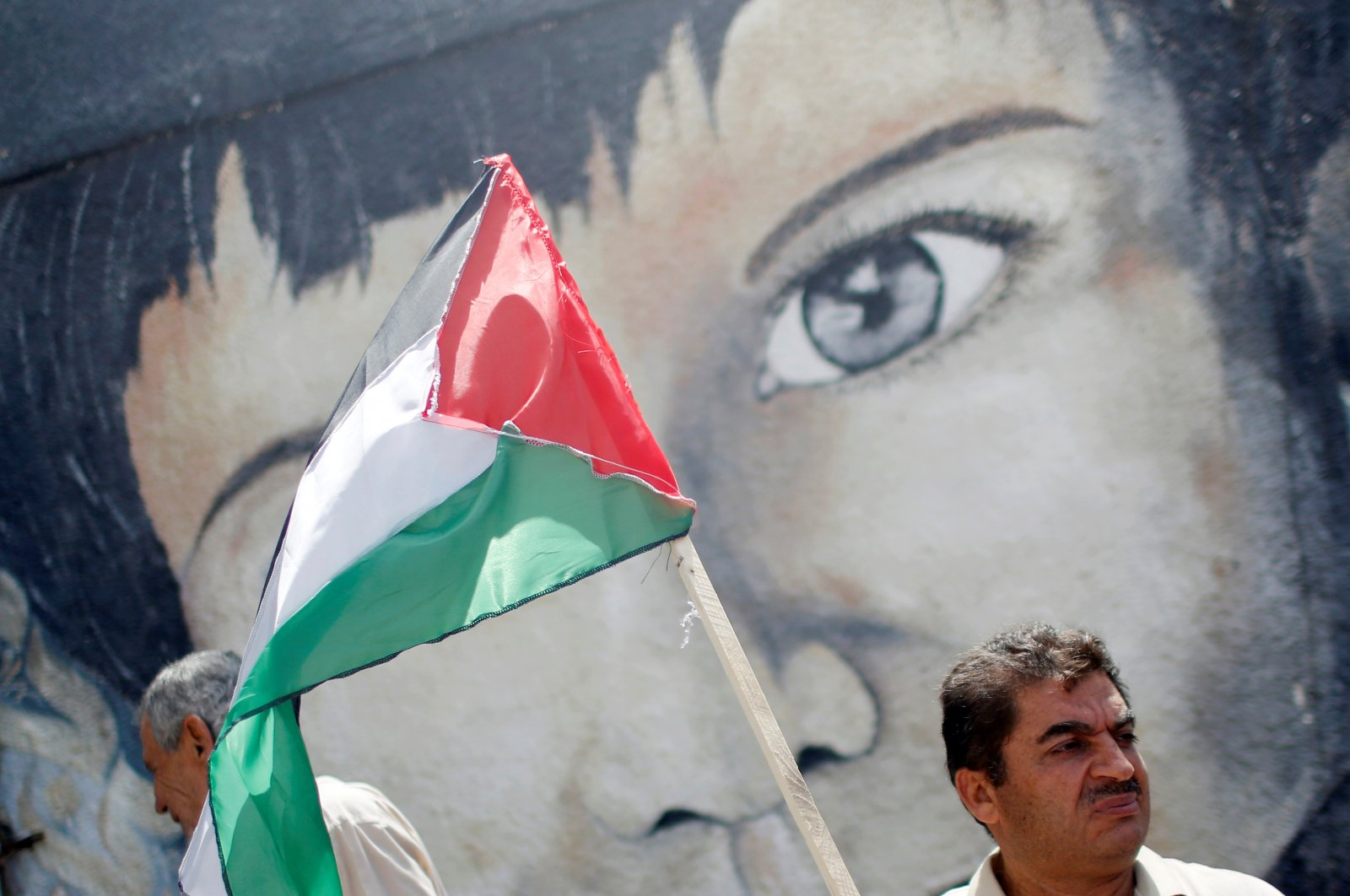 A demonstrator holding a Palestinian flag stands in front of a mural during a protest against Israel's plan to annex parts of the occupied West Bank, Gaza City, Palestine, June 22, 2020. (Reuters Photo)