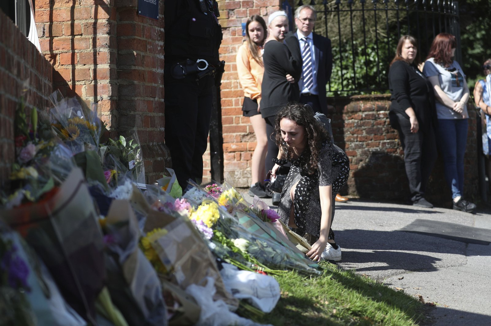 Flowers are placed at the entrance to the Holt School in memory of teacher James Furlong, a victim of a terror attack in nearby Reading, in Wokingham, England, June 22, 2020. (AP Photo)