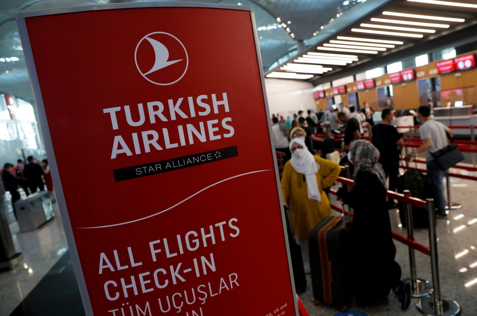 Passengers wearing protective face masks line up to check in for a flight to Washington, D.C., at the Istanbul Airport, during the first day of resumed Turkish Airlines flights to the U.S. amid the coronavirus pandemic, in Istanbul, Turkey June 19, 2020. (Reuters Photo)
