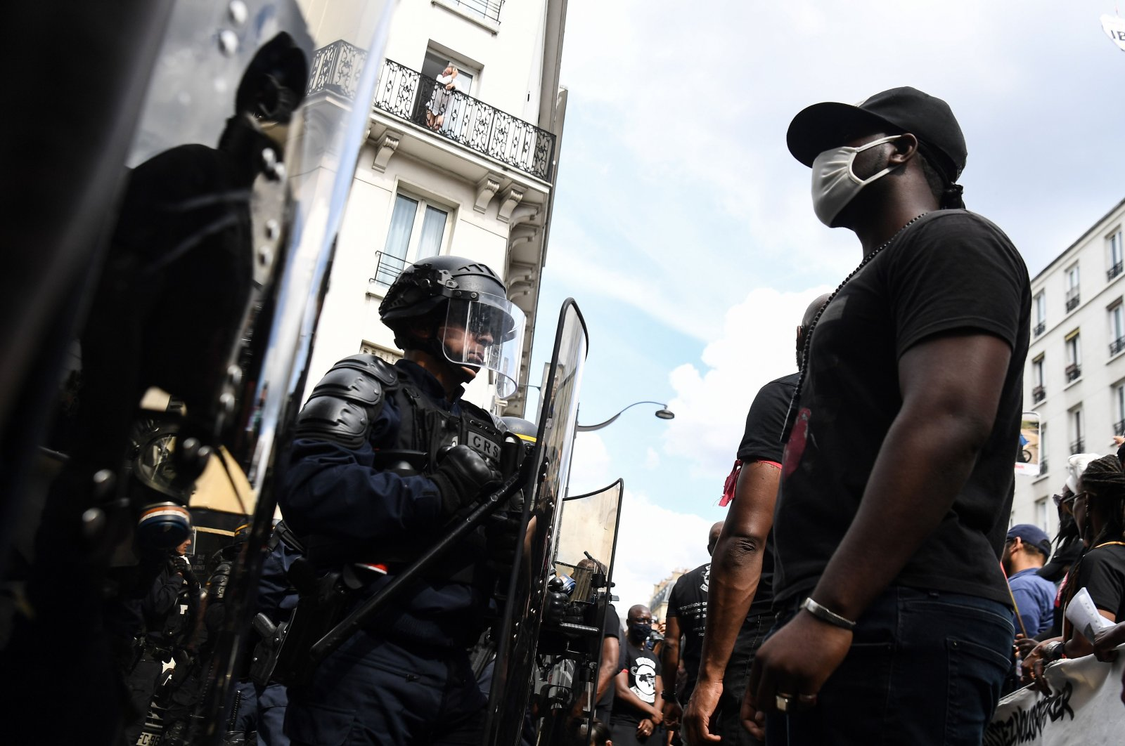 A protester wearing a face mask stands in front of police during a demonstration against racism and police brutality and in memory of Lamine Dieng, a French-Senegalese 25 year-old who died after his arrest in 2007, in Paris, June 20, 2020. (AFP File Photo)