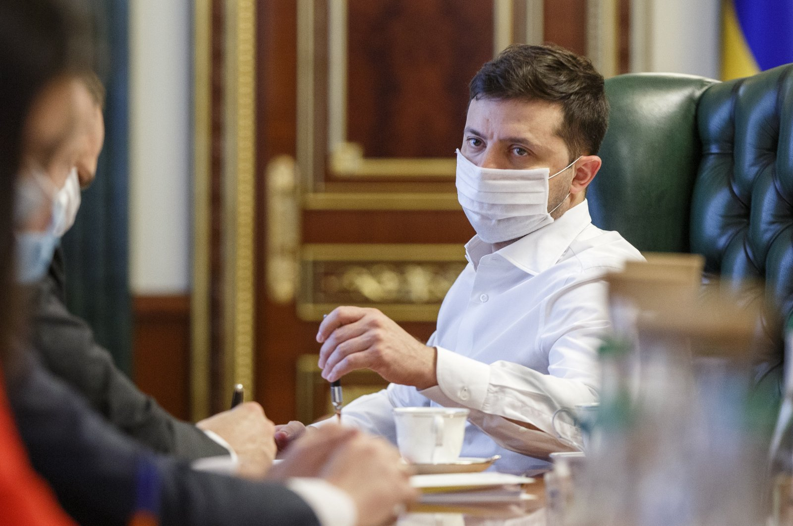 Ukrainian President Volodymyr Zelenskiy in a face mask to protect against coronavirus, discusses the COVID-19 situation in the country with officials in his office in Kyiv, Ukraine on April 22, 2020. (AP Photo)