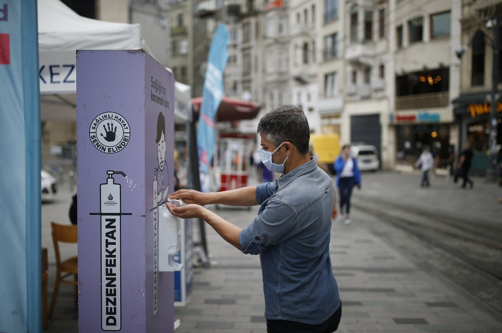 A man wearing a face mask uses disinfectant from a public station on Istiklal street near Taksim Square in Istanbul, Turkey, June 18, 2020. (AP Photo)