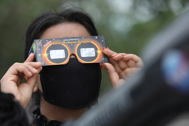 Un jeune Indien portant un masque facial essaie d'avoir un aperçu d'une éclipse solaire partielle annulaire à l'aide de lunettes de protection spéciales par temps nuageux dans le village de Sakoh, près de Dharamsala, dans le nord de l'Inde, le 21 juin 2020. (Photo EPA)