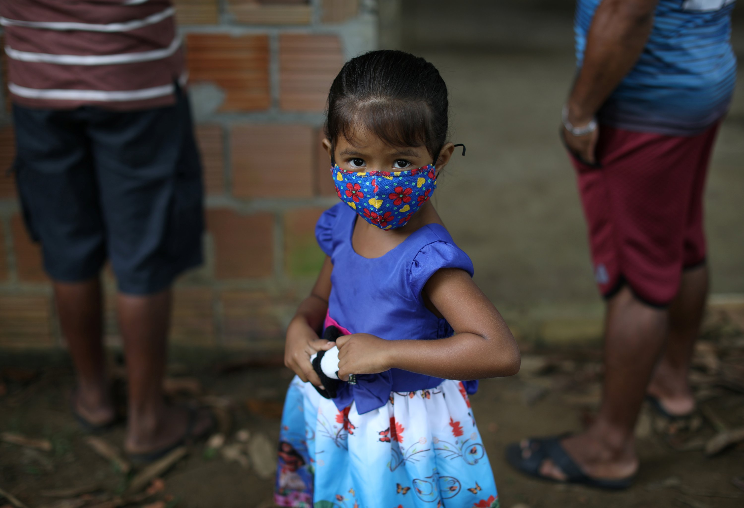 A child wearing a protective face mask waits to be tested for the coronavirus in the Bela Vista do Jaraqui, in the Conservation Unit Puranga Conquista along the Negro River banks, where Ribeirinhos (forest dwellers) live, in Manaus, Brazil, May 29, 2020. (Reuters Photo)