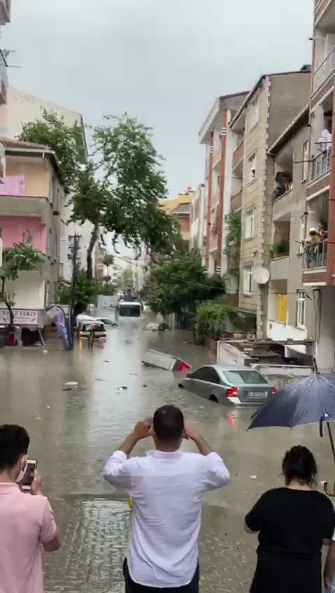 İnsanlar 23 Haziran 2020 İstanbul Esenyurt'taki sel baskınlarının fotoğrafını çekiyor. (DHA Fotoğraf)