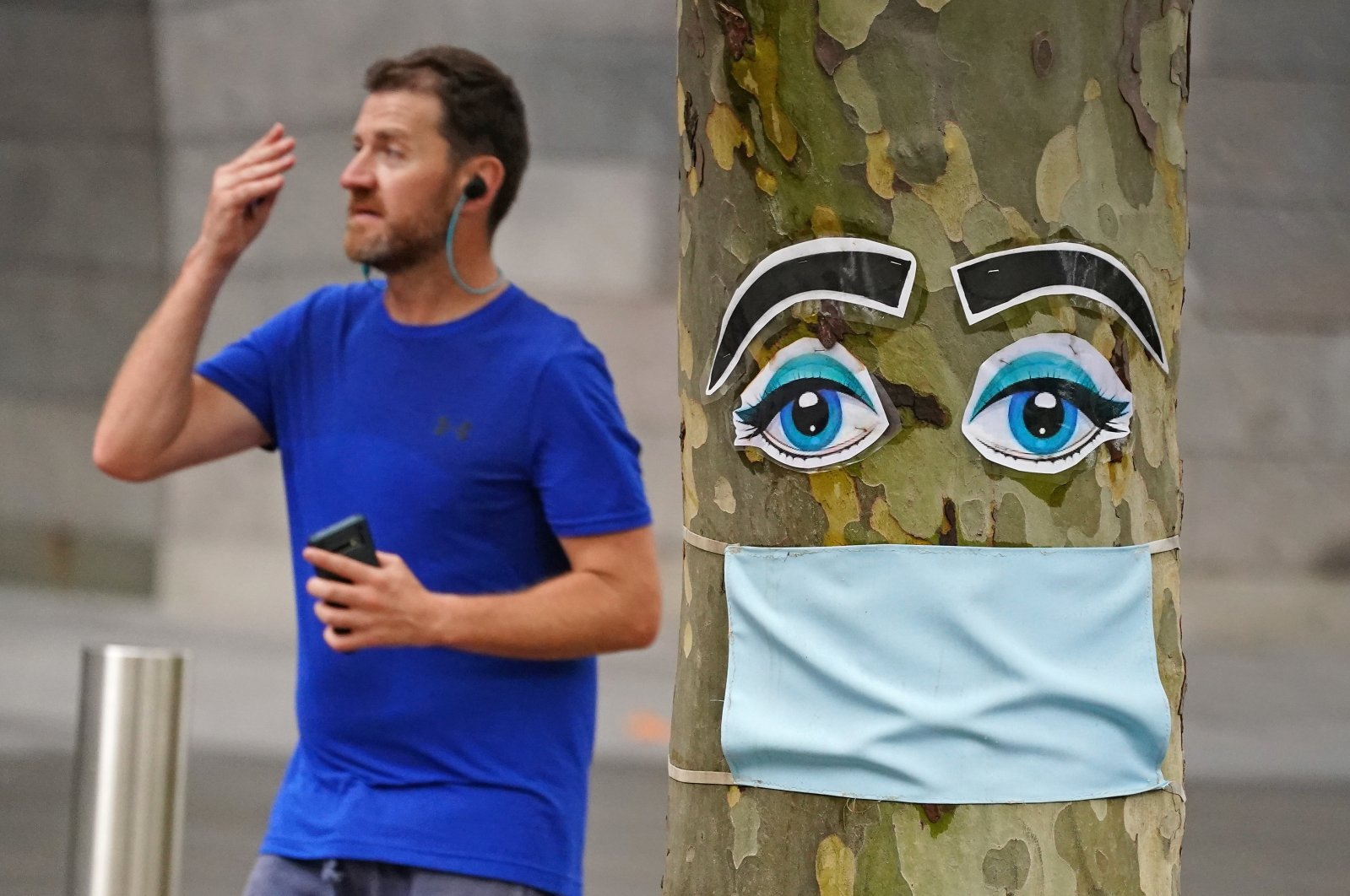 A man walks past a tree with a face mask and eyes stapled to it in Melbourne, Australia, April 26, 2020. (AAP Image via Reuters)