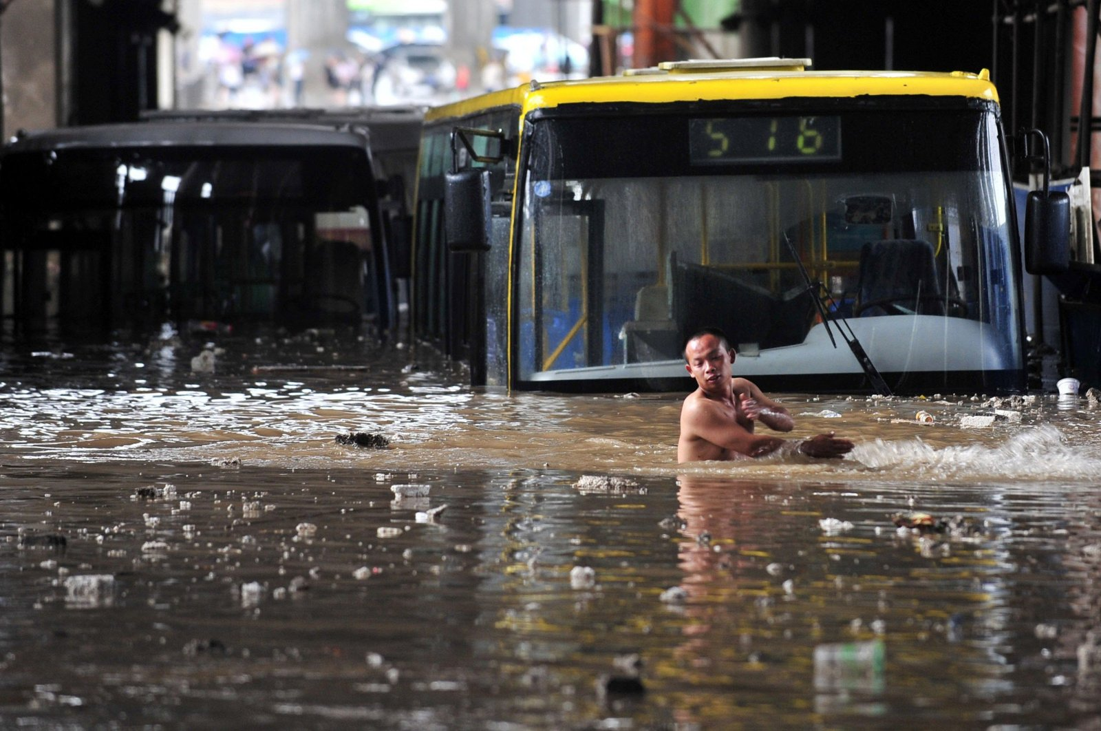 A driver wades through floodwater after his bus was stranded in a flooded tunnel in Wuhan, Hubei province June 18, 2011. (Reuters Photo)