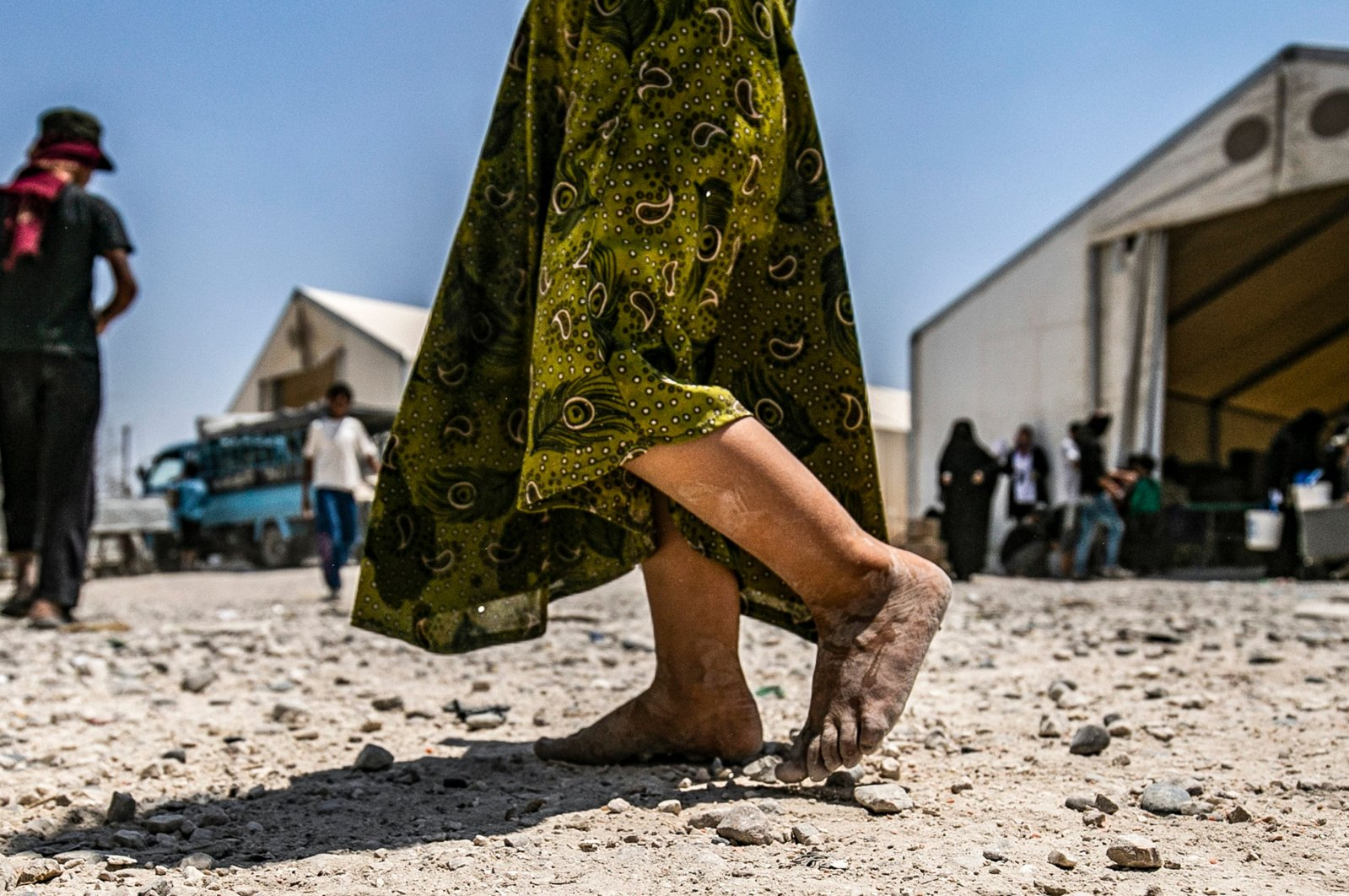 A young child walks barefoot at al-Hol camp for displaced people, in al-Hasakeh governorate, north-eastern Syria, July 22, 2019. (AFP)