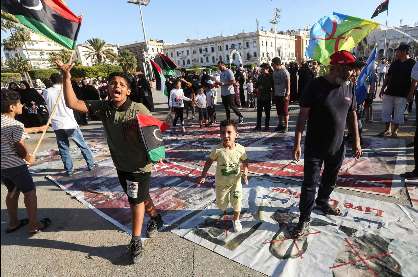 "Children wave flags of Libya as they walk on protest signs showing ""X"" marks on the faces of (R to L) French President Emmanuel Macron, Egyptian President Abdel-Fattah el-Sissi and Abu Dhabi's Crown Prince Sheikh Mohammed bin Zayed Al Nahyan, in the Martyrs' Square in the center of the Libyan capital Tripoli, June 21, 2020. (AFP Photo)"