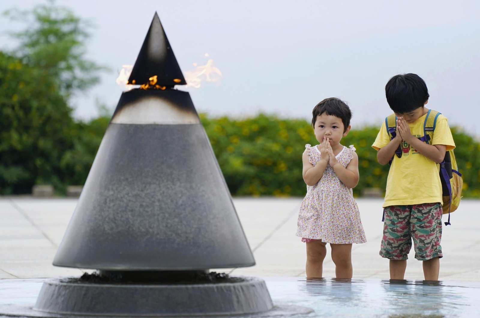 """Children pray in front of the """"Peace of Fire"""" at the Peace Memorial Park in Itoman, Okinawa, Japan, June 23, 2020. (AP Photo)"""
