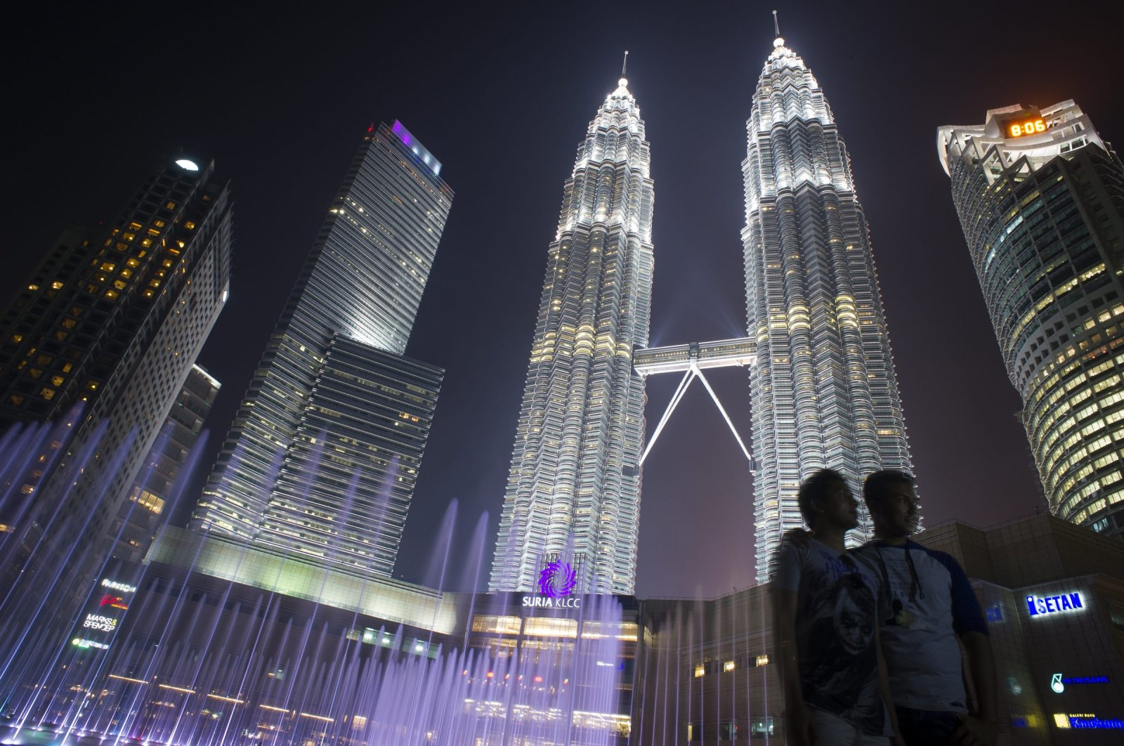 Tourists have their photograph taken in front of the Petronas Twin Towers in Kuala Lumpur, Malaysia, March 10, 2015. (AP Photo)