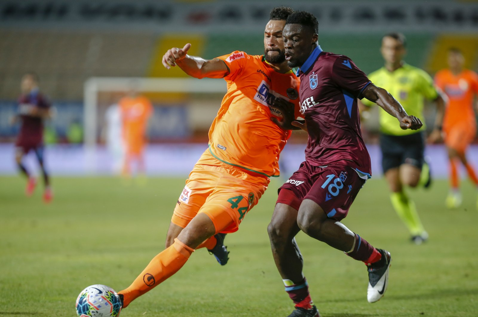 Alanyaspor's Steven Caulker and Trabzonspor's Caleb Ekuban vie for the ball during a Süper Lig match in Antalya, Turkey, June 22, 2020. (AA Photo)