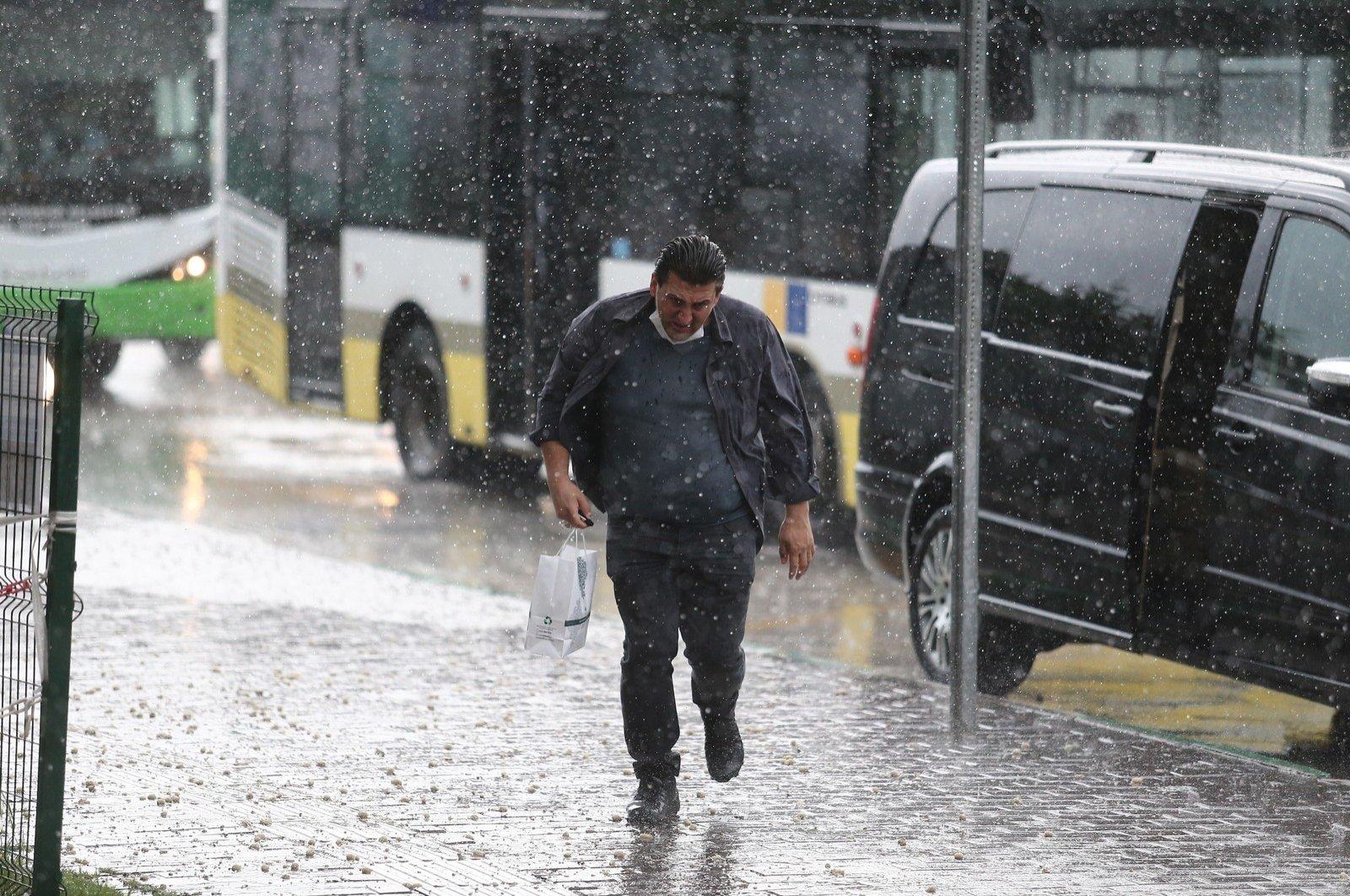 A man runs for cover under heavy rain in Bursa, Turkey, June 23, 2020. (IHA Photo)