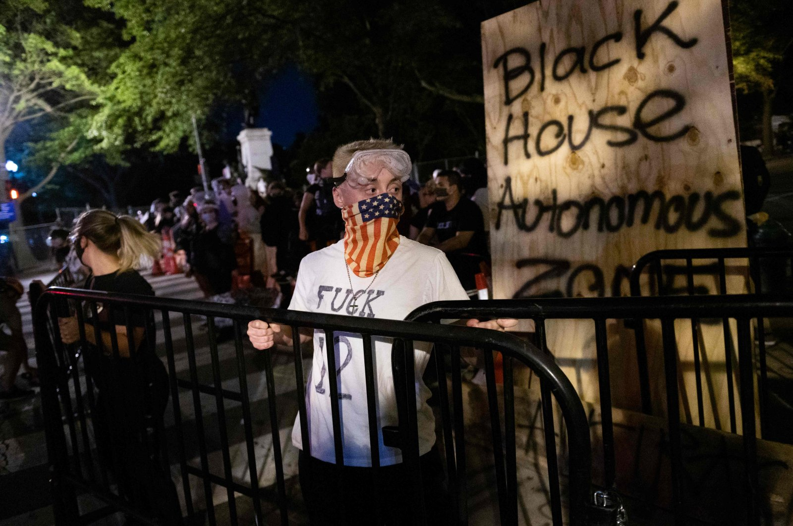 """Protesters carry metal stanchions as they fortify a barricade they erected and marked with the sign """"Black House Autonomous Zone"""" in front of Lafayette Park near the White House, in Washington, D.C., U.S., June 22, 2020. (AFP Photo)"""