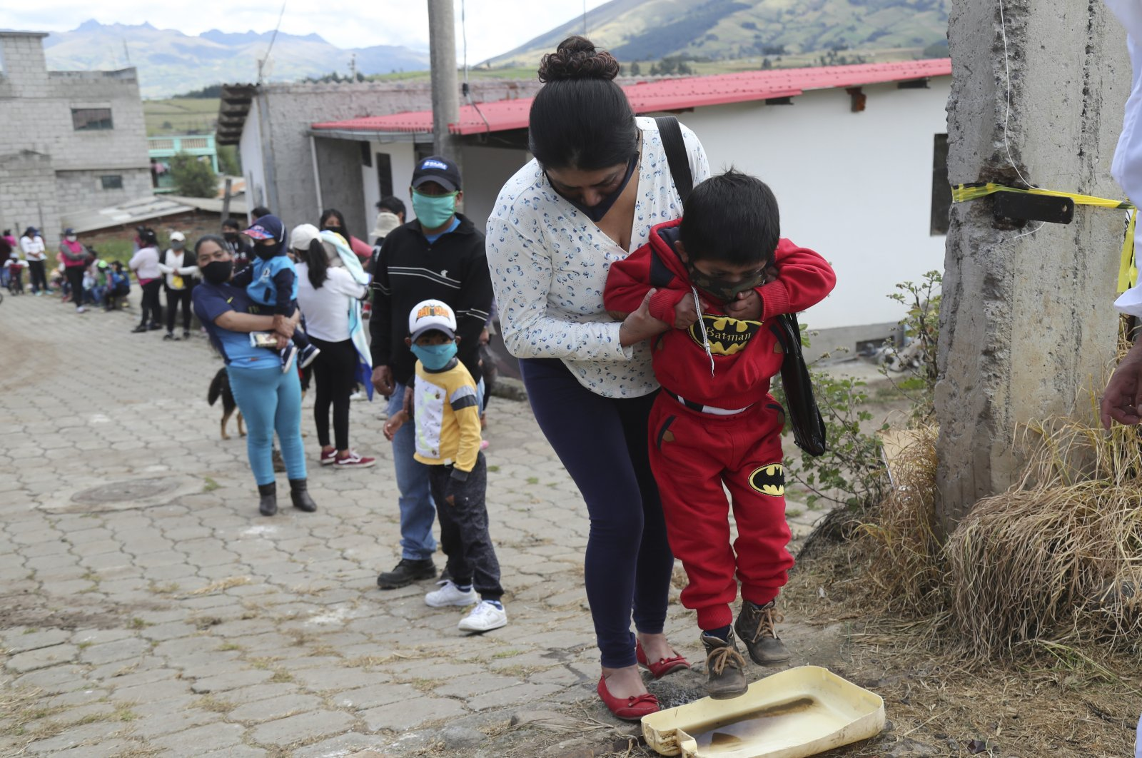 A woman helps her son to disinfect his shoes before entering the Cariacu stadium, Ecuador, June 17, 2020. (AP Photo)