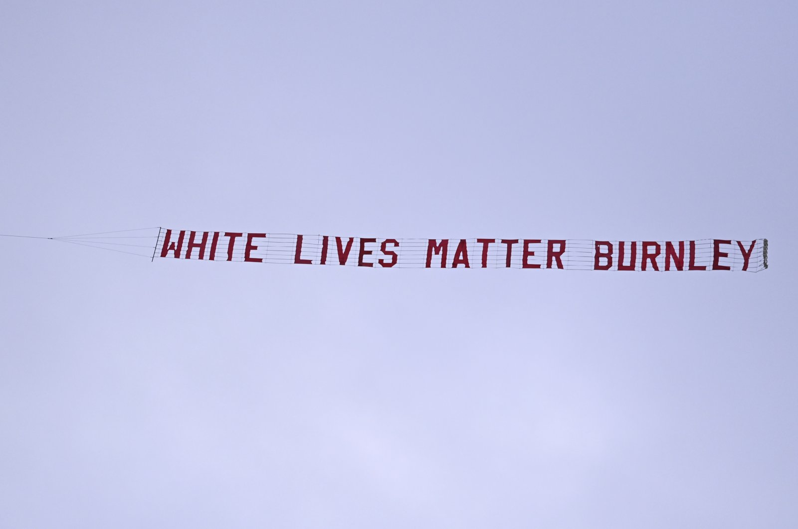 A plane towing a banner reading White Lives Matter Burnley flies above the stadium during the during the English Premier League football match between Manchester City and Burnley at Etihad Stadium, in Manchester, England, Monday, June 22, 2020. (AP Photo)