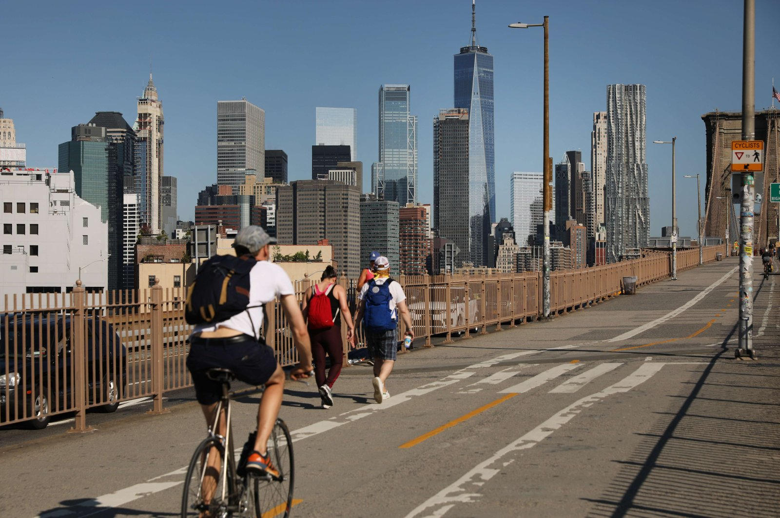 People are seen at the Brooklyn Bridge as Manhattan enters Phase 2 of reopening following restrictions imposed to curb the coronavirus pandemic, in New York, June 22, 2020. (Getty Images via AFP)