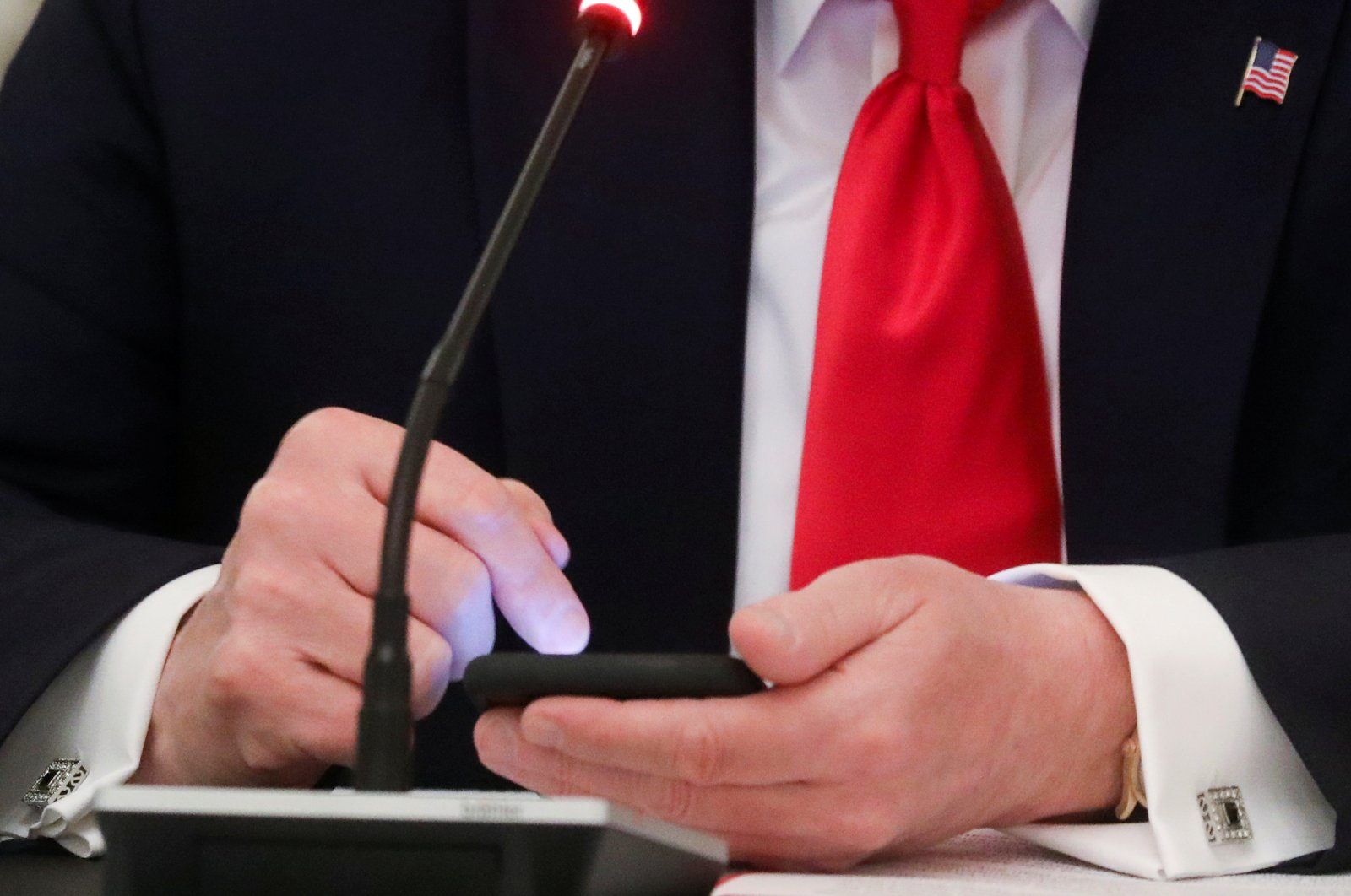 U.S. President Donald Trump taps the screen on a mobile phone at the approximate time a tweet was released from his Twitter account, during a roundtable discussion on the reopening of small businesses in the State Dining Room at the White House in Washington, U.S., June 18, 2020. (Reuters Photo)