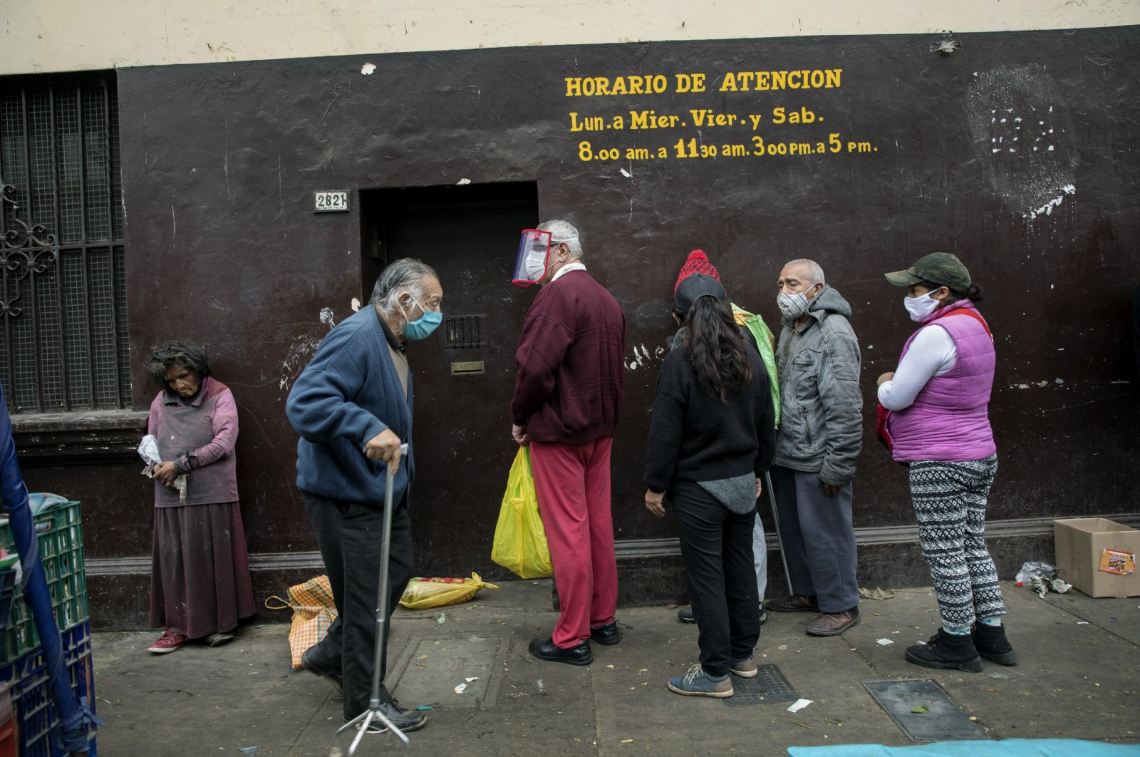 People wait in a line to receive free food at La Parada market in La Victoria district of Lima, Peru, Tuesday, June 23, 2020. (AP Photo)
