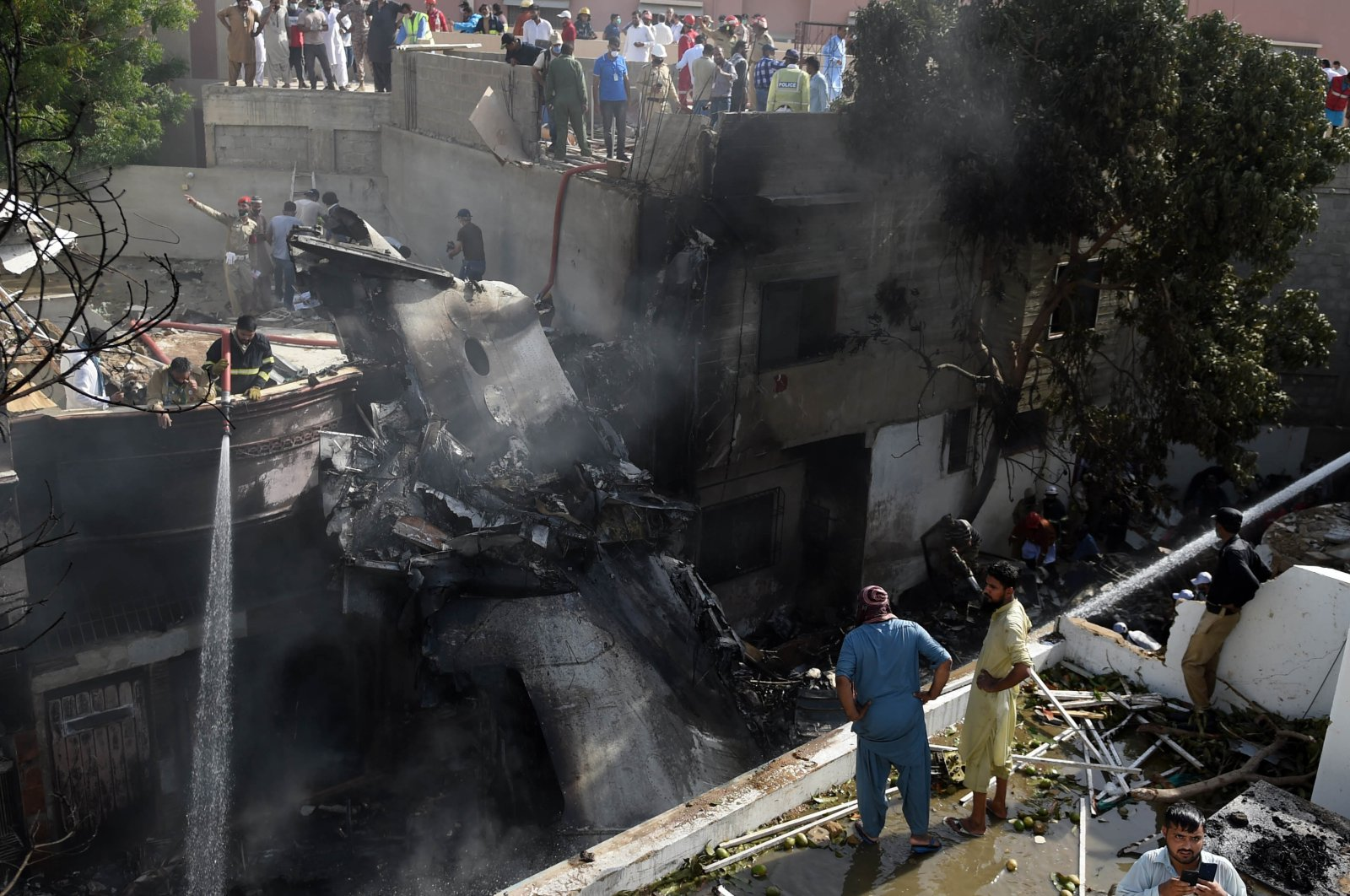 Locals inspect the wreckage of a passenger plane of state-run Pakistan International Airlines, at the scene after it crashed in a residential area, in Karachi, Pakistan, May 22, 2020. (EPA-EFE Photo)