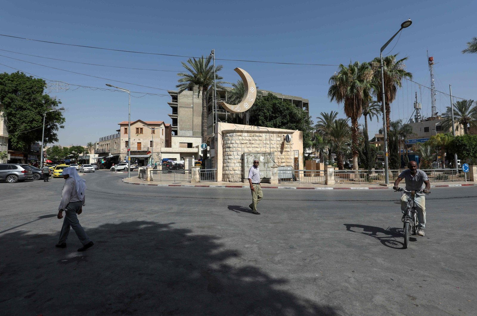 Palestinians pass by on a street in the occupied West Bank city of Jericho, Palestine, June 21, 2020. (AFP Photo)