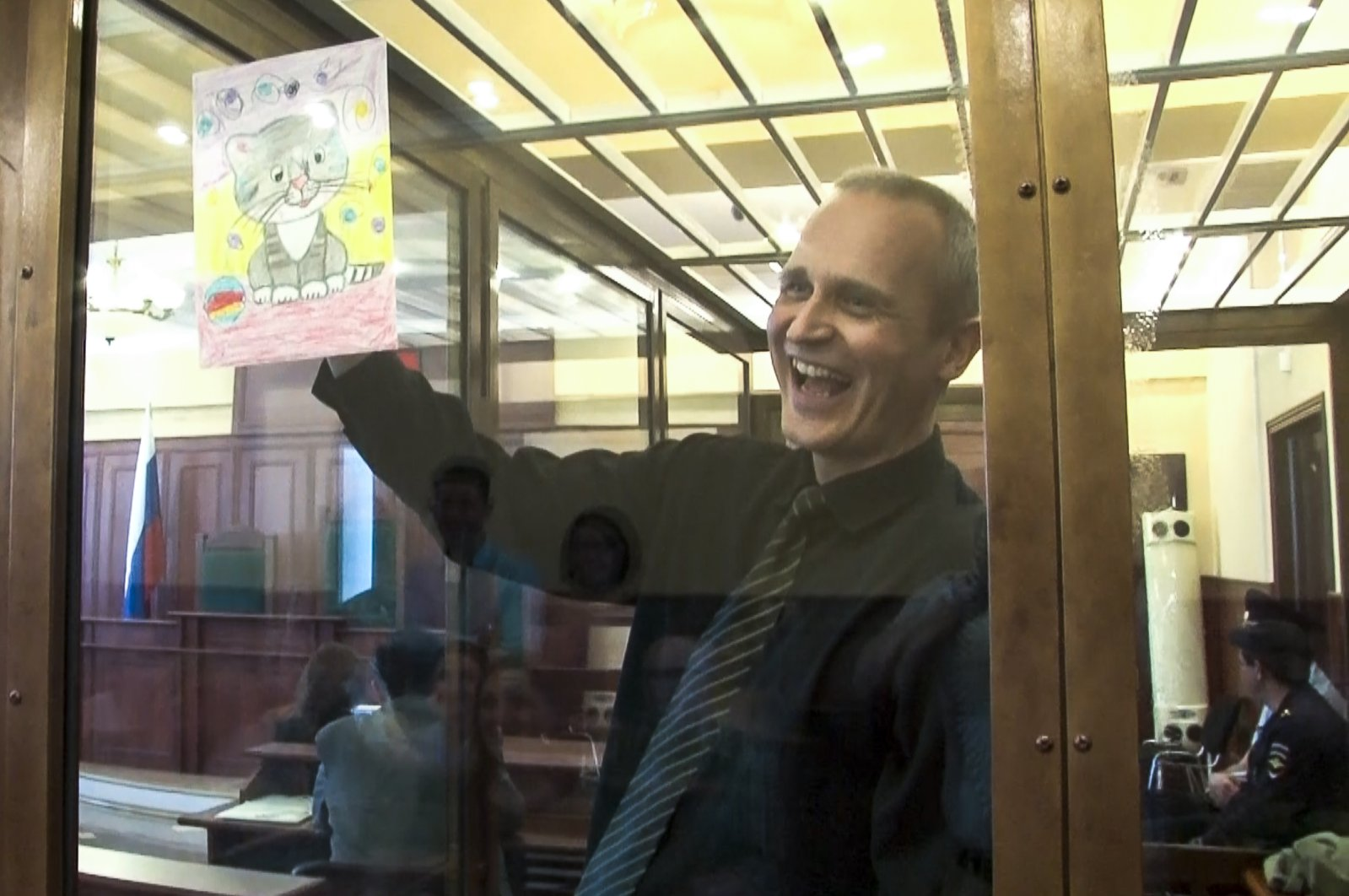 In this file image taken from video, Dennis Christensen shows a picture in a courtroom in Oryol, Russia, May 23, 2019. (AP Photo)
