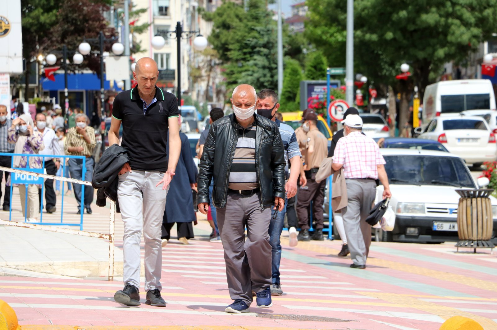 A man wearing a mask walks next to another man not wearing a mask in Yozgat, Turkey, June 23, 2020. (IHA Photo)