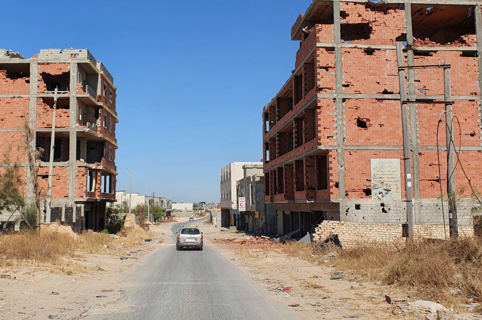 A car advances on an empty road between damaged buidlings in the Salaheddin district south of the Libyan capital Tripoli, June 21, 2020. (AFP)
