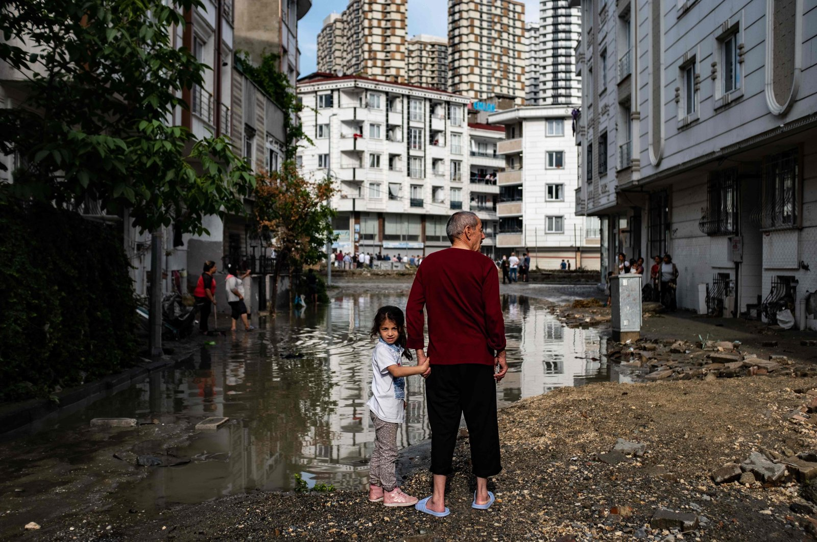 A man and a child stand in a flooded street in the Esenyurt district, Istanbul, Turkey, June 23, 2020. (AFP Photo)