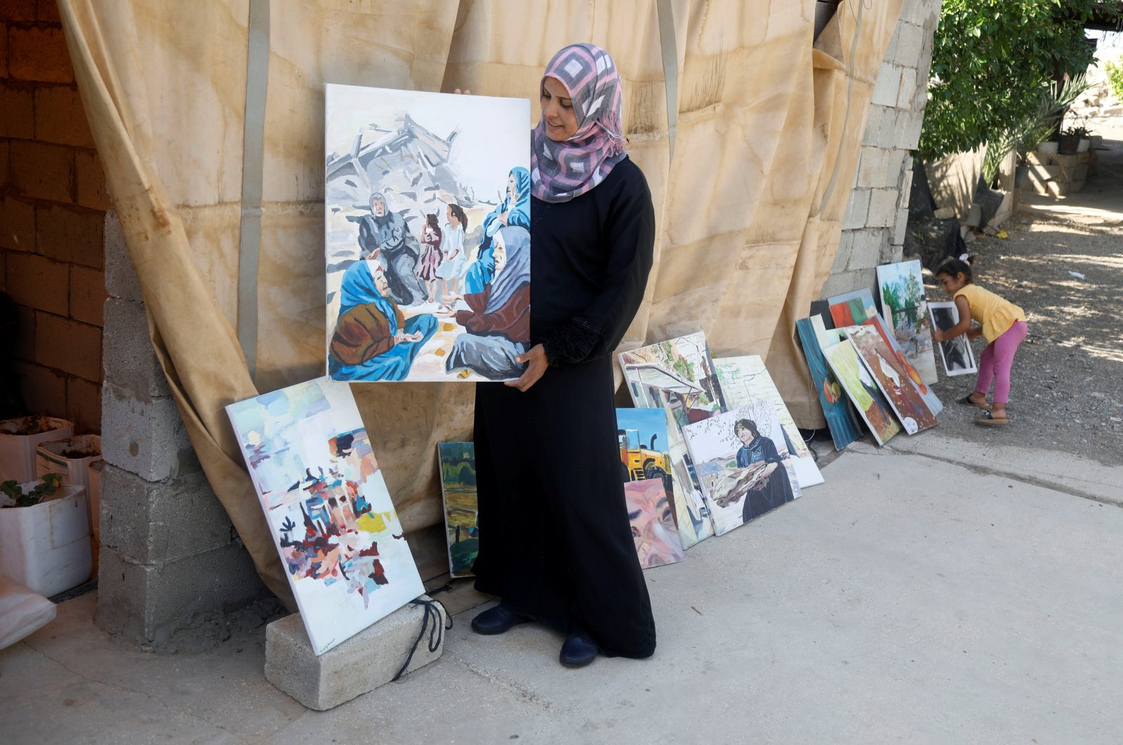 Khadeeja Bisharat, a Palestinian artist, displays a conflict-inspired artwork she painted, in Jordan Valley in the Israeli-occupied West Bank, June 18, 2020. (Reuters Photo)