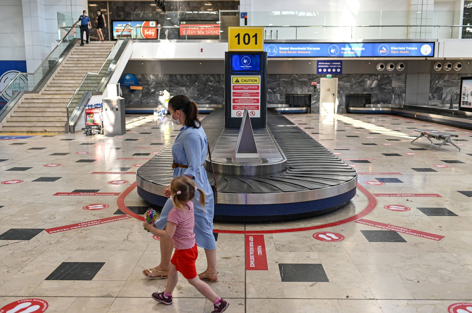 """A woman walks with her daughter beside a luggage belt as stickers on the ground read """"Keep your social distance"""" at Antalya Airport in Antalya, a popular holiday resort city in southern Turkey, June 19, 2020. (AFP Photo)"""