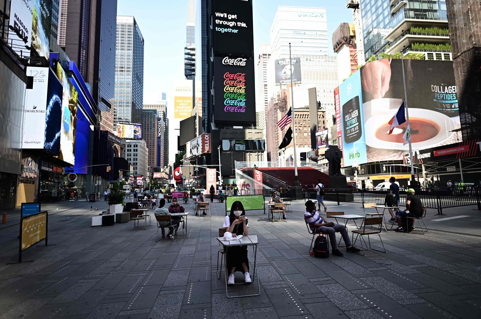 People sit at tables, respecting social distancing, in Times Square as New York City enters phase two of reopening, New York, U.S., June 22, 2020. (AFP Photo)