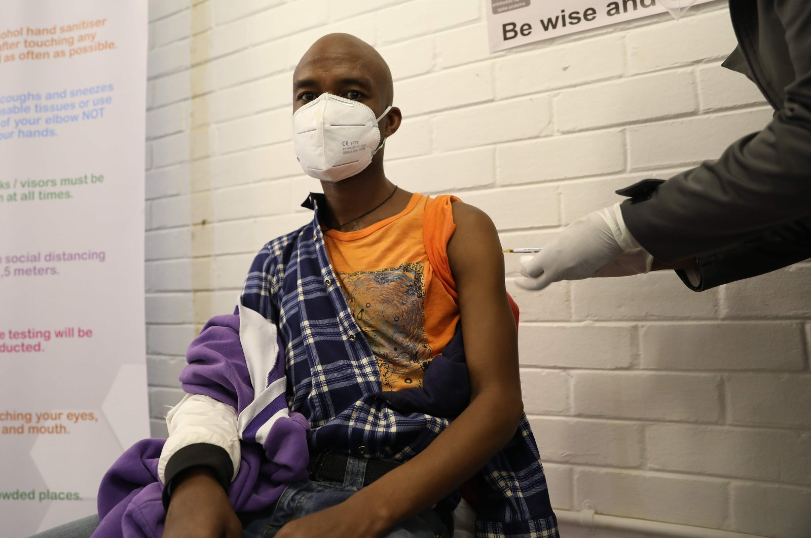 One of the first South African Oxford vaccine trialists looks on as a medical worker injects him with the clinical trial for a potential vaccine against COVID-19 at the Baragwanath hospital, Soweto, South Africa, June 24, 2020. (AFP Photo)