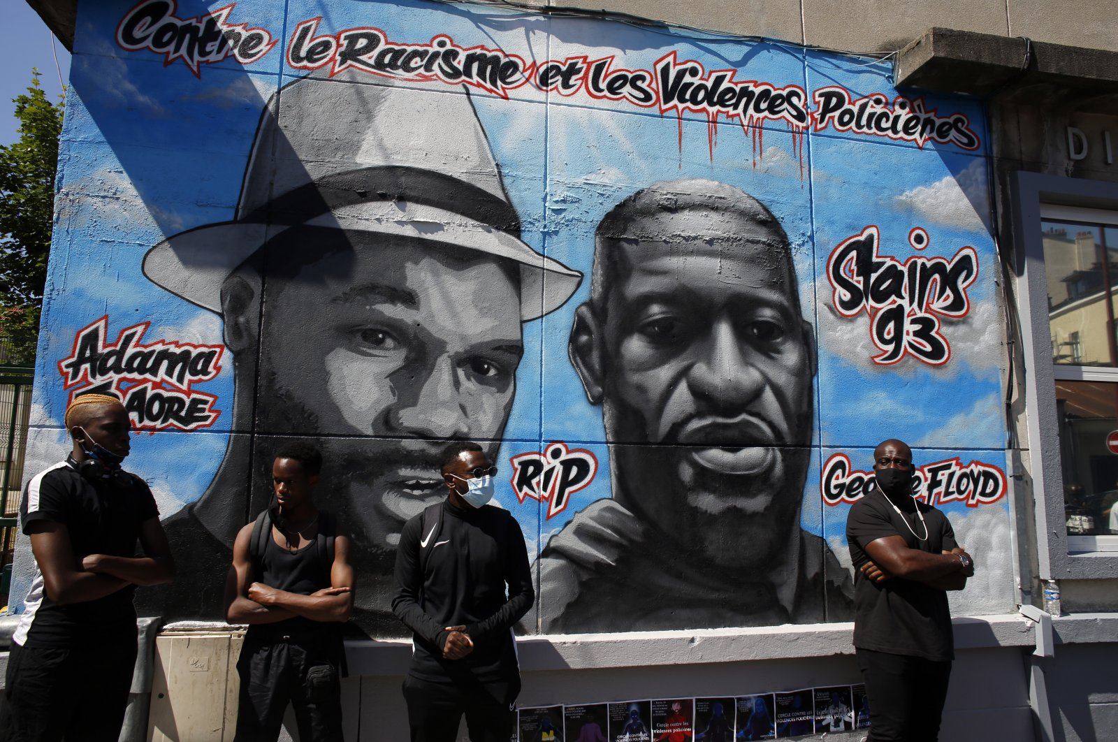 People stand in front of a mural showing Adama Traore, left, and George Floyd, Stains, June 22, 2020. (AP Photo)