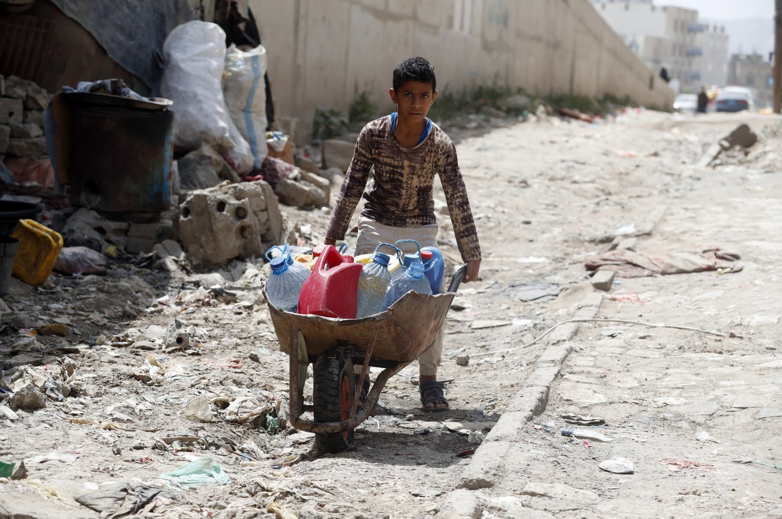 A young boy pushes a wheelbarrow with water bottles after filling them from a charity tap, in Sanaa, Yemen, June 18, 2020. (EPA Photo)